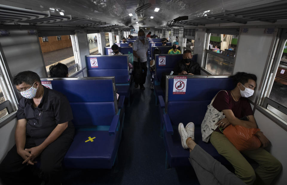 Passengers on a train with staggered seating wear face masks to curb the spread of the coronavirus at the Hua Lamphong Railway Station in Bangkok, Thailand, Tuesday, June 9, 2020. The Thai government continues to ease restrictions related to running business in capital Bangkok that were imposed weeks ago to combat the spread of COVID-19. (AP Photo/Sakchai Lalit)