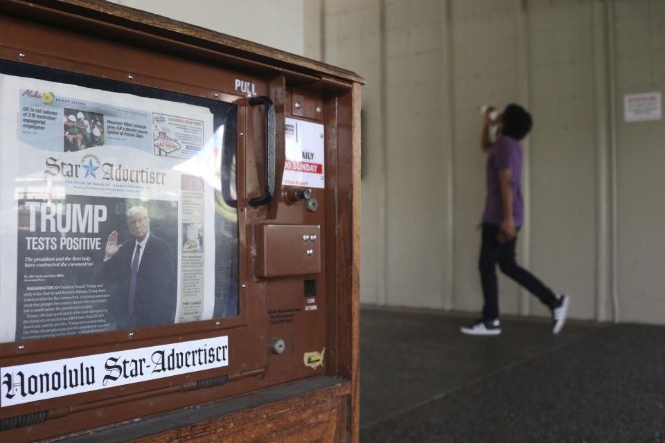 A man walks past a newspaper stand at the international airport in Honolulu on Friday, Oct. 2, 2020. After a summer marked by a surge of coronavirus cases in Hawaii, officials plan to reboot the tourism based economy later this month despite concerns about the state's pre-travel testing program. (AP Photo/Caleb Jones)