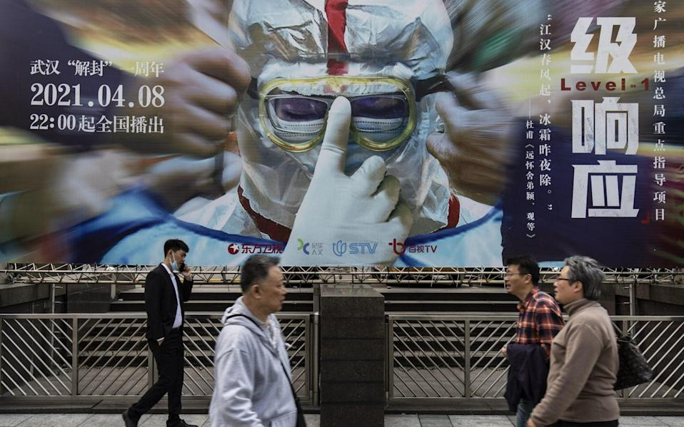 Pedestrian walk past a billboard promoting a television show on China's fight against Covid-19 in Shanghai - Bloomberg