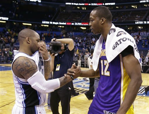 Former teammates Orlando Magic's Jameer Nelson, left, and Los Angeles Lakers' Dwight Howard (12) shake hands before leaving the court at the end of an NBA basketball game, Tuesday, March 12, 2013, in Orlando, Fla. Los Angeles won the game 106-97.(AP Photo/John Raoux)