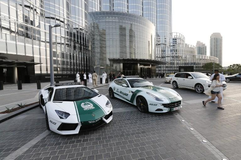 "A picture taken on April 25, 2013 shows Lamborghini (L) and Ferrari police vehicles at the foot of the Burj Khalifa tower in the Gulf emirate of Dubai. Two weeks after introducing the Lamborghini police car, Dubai Police has introduced a Ferrari to the fleet, to further strengthen the ""image of luxury and prosperity"" of the emirate. AFP  PHOTO /  KARIM SAHIB"