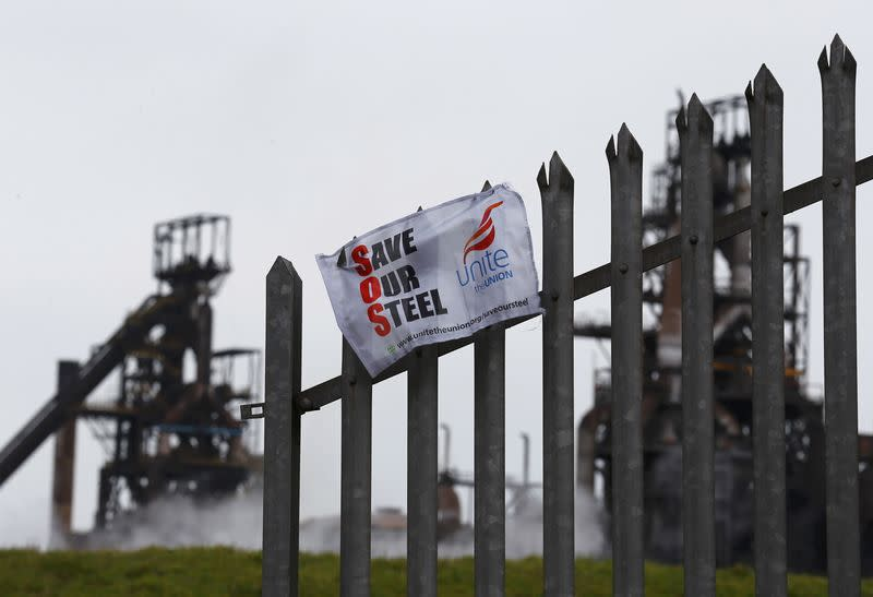 A union banner hangs from a fence in front of the Tata steelworks in the town of Port Talbot