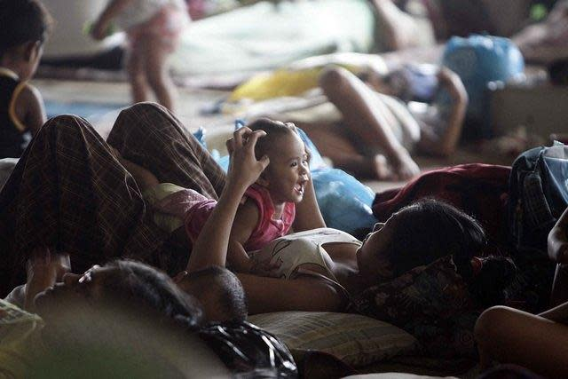 "A mother and her child tries to get some playtime inside an evacuation center at Barangay Malanday in low-lying Marikina City, northeast of Manila, despite rising floodwaters from continuous rains brought on by Typhoon 'Gener'. Marikina City officials are starting to prepare to forcibly evacuate residents from some high-risk areas after the water level at the Marikina River rose to 16 meters early today, raising the alert level at the river to ""2."" (Mike Alquinto/NPPA Images)"