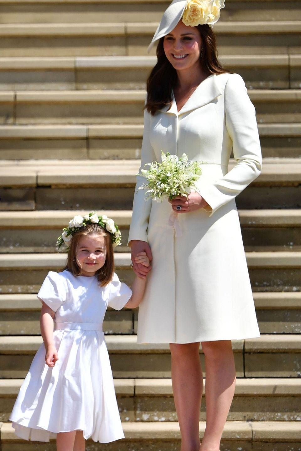 <p>Princess Charlotte holds the Duchess of Cambridge's hand outside St. George's Chapel as they wish the newlyweds off in their horse-drawn carriage. </p>
