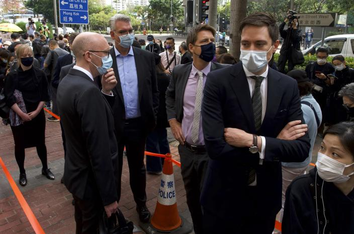 From front left at front, Charles Whiteley, Deputy Head of Office, EU Office, Johannes Harms, Consul of Germany, Joakim Ladeborn, Deputy Consul General of Sweden, Rogier Hekking, Deputy Consul General of Netherlands queue up outside a court to try get in for the hearing in Hong Kong Monday, March 1, 2021. People gathered outside the court Monday to show support for 47 activists who were detained over the weekend under a new national security law that was imposed on the city by Beijing last year. (AP Photo/Vincent Yu)
