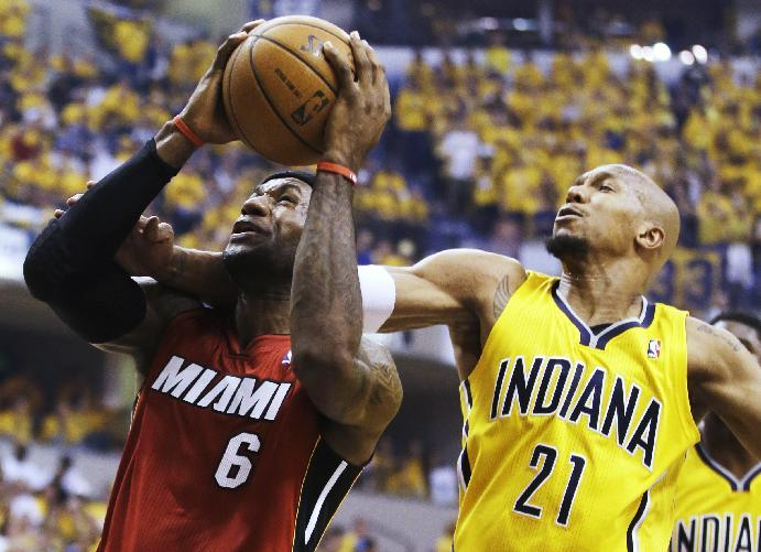 Indiana Pacers forward David West (21) tries to stop a shot by Miami Heat forward LeBron James (6) during the first half of Game 1 of the Eastern Conference finals NBA basketball playoff series Sunday, May 18, 2014, in Indianapolis.  (AP Photo/Darron Cummings)