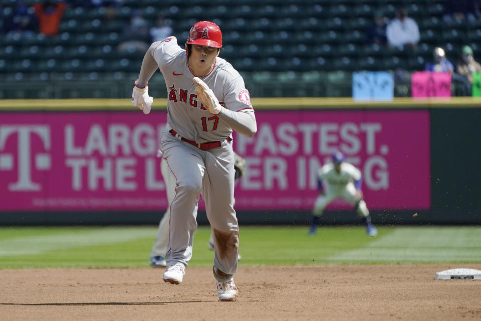 Los Angeles Angels' Shohei Ohtani (17) takes off to safely steal third base during the first inning of a baseball game against the Seattle Mariners, Sunday, May 2, 2021, in Seattle. (AP Photo/Ted S. Warren)