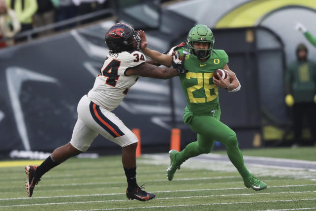 Oregon running back Travis Dye (26) tries to avoid Oregon State inside linebacker Avery Roberts (34) during the second half of an NCAA college football game in Eugene, Ore., Saturday, Nov. 30, 2019. (AP Photo/Amanda Loman)