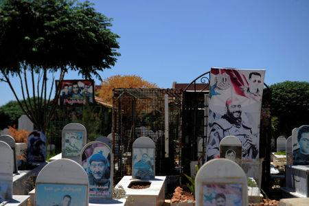 A view of graves at a cemetery in the district of Zahraan in Homs city