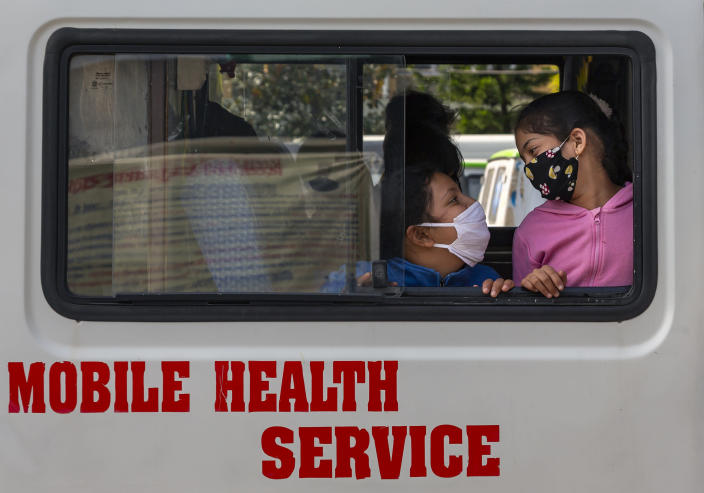 Children wearing masks to protect themselves against the coronavirus wait inside an ambulance for anti-rabies vaccine shots in Dharmsala, India, Thursday, Oct. 29, 2020. India's confirmed coronavirus caseload surpassed 8 million on Thursday with daily infections dipping to the lowest level this week, as concerns grew over a major Hindu festival season and winter setting in. (AP Photo/Ashwini Bhatia)