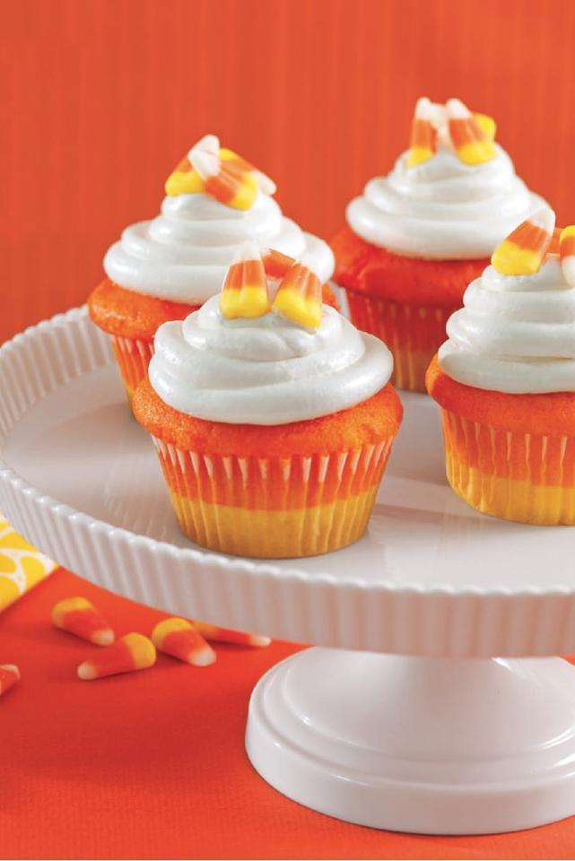 """<p>To get this perfect gradient of color, top yellow-colored batter with orange batter and then decorate with white frosting. </p><p><em><a href=""""https://www.womansday.com/food-recipes/food-drinks/a28835151/candy-corn-cupcakes-recipe/"""" target=""""_blank"""">Get the recipe for Candy Corn Cupcakes.</a></em></p>"""
