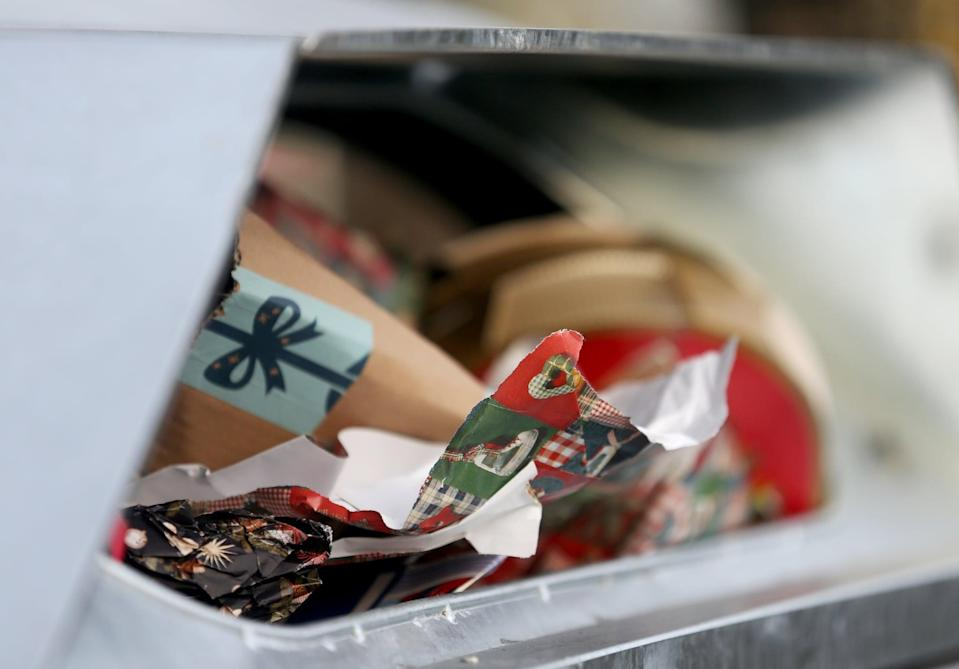 27 December 2018, North Rhine-Westphalia, Essen: A garbage container is filled to the brim with Christmas gift paper. If the wrapping paper is made of coated paper, it should be disposed of in the yellow bin. Photo: Roland Weihrauch/dpa (Photo by Roland Weihrauch/picture alliance via Getty Images)
