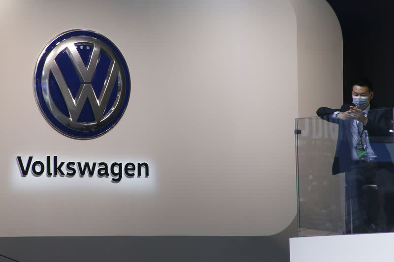 A man is seen next to the logo of Volkswagen at the booth of Shanghai Volkswagen, a joint venture between SAIC Motor and Volkswagen Group, during the Auto China 2016 auto show in Beijing