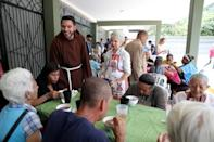 Venezuelan priest Luis Antonio Salazar talks to local residents as they receive a charity lunch at Chiquinquira Catholic church in Caracas