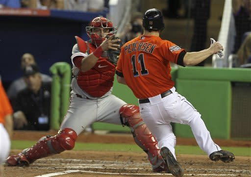 Philadelphia Phillies catcher Carlos Ruiz (51) tags Miami Marlins runner Bryan Peterson (11) out at home during the fourth inning of a MLB baseball game in Miami, Sunday, Sept. 30, 2012. (AP Photo/J Pat Carter)