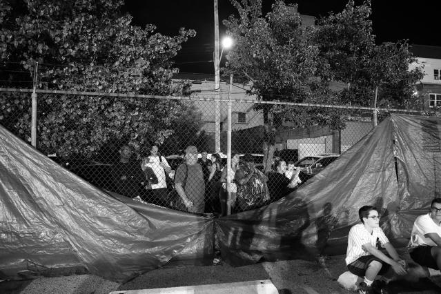<p>People from the neighborhood watched through a spot where the blue tarp blocking the view had come loose, at the Brooklyn Smoker on Aug. 24, 2017. (Photo: Gordon Donovan/Yahoo News) </p>