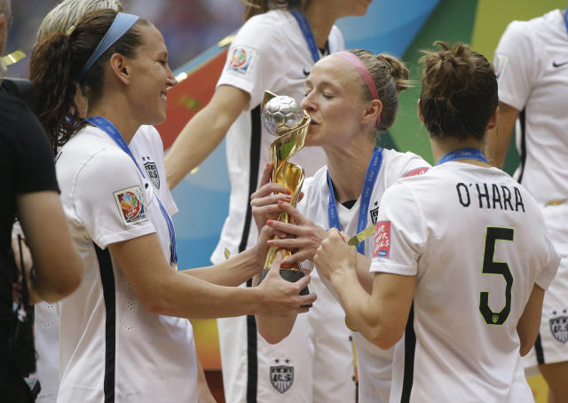 FILE - In this July 5, 2015, file photo, United States' Becky Sauerbrunn kisses the trophy as Lauren Holiday, left, and Kelley O'Hara, right, look on after the U.S. beat Japan 5-2 in the FIFA Women's World Cup soccer championship in Vancouver, British Columbia, Canada. If the defending champions make the field for soccers premier event in France next year, it will be Sauerbrunns third World Cup. (AP Photo/Elaine Thompson, File)