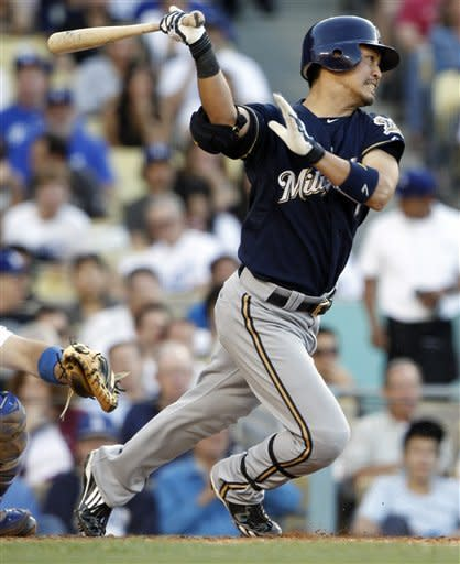 The Milwaukee Brewers' Norichika Aoki, of Japan, swings and is safe at first on a throwing error by Los Angeles Dodgers pitcher Javy Guerra in the sixth inning of a baseball game in Los Angeles Monday, May 28, 2012.(AP Photo/Reed Saxon)