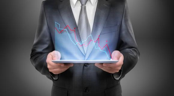 Businessman holding a tablet projecting a falling graph.