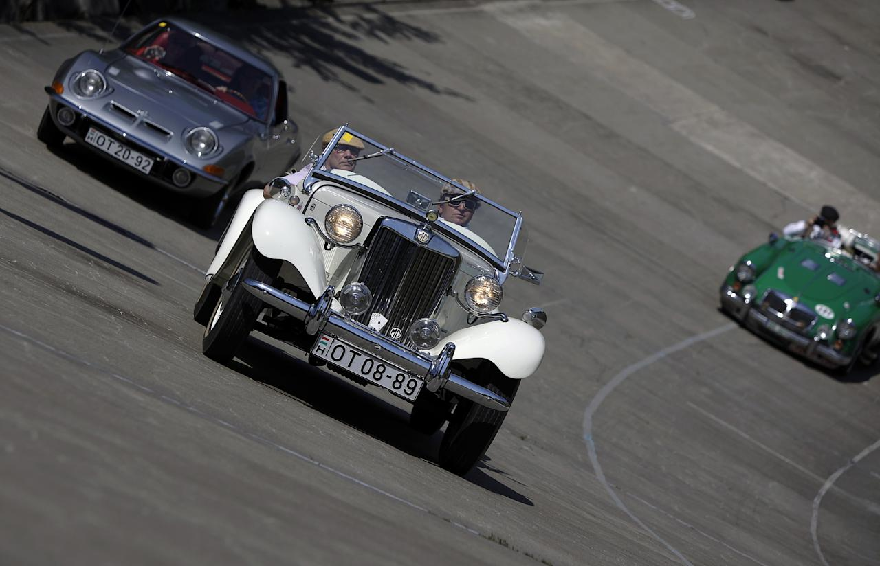Drivers drive lead their vehicle on an oval track of a velodrome during an old timer car and motorcycle show in Budapest on May 1, 2012. The event brought life again into the 412 meter long Millennial Velodrome of Budapest, which was built in 1896 and is one of the oldest arenas for track cycling in Europe.  AFP PHOTO / PETER KOHALMIPETER KOHALMI/AFP/GettyImages
