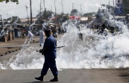 Policeman walks after throwing a teargas canister during a protest against Burundi President Pierre Nkurunziza and his bid for a third term in Bujumbura
