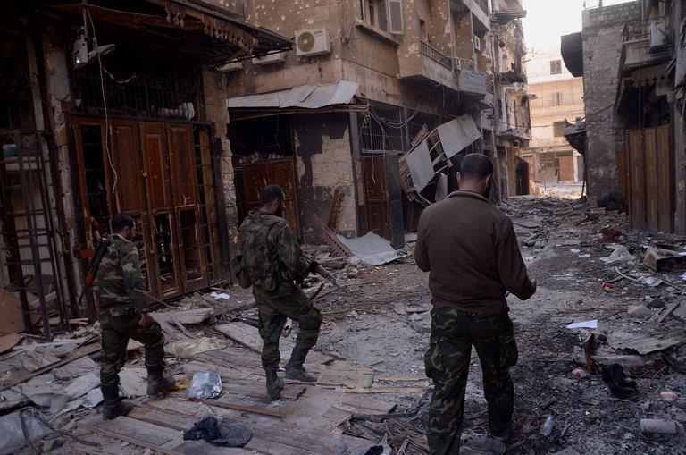 Syrian government forces walk through Aleppo's old souk on January 3, 2012, after they allegedly recaptured the area