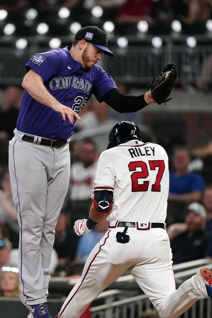 Atlanta Braves' Austin Riley (27) is safe at first base as Colorado Rockies first baseman C.J. Cron (25) handles the wild throw from shortstop Trevor Story in the sixth inning of a baseball game Tuesday, Sept. 14, 2021, in Atlanta. (AP Photo/John Bazemore)