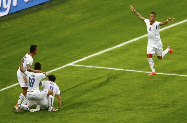 Chile players celebrate after scoring a goal during the 2014 World Cup Group B soccer match between Spain and Chile at the Maracana stadium
