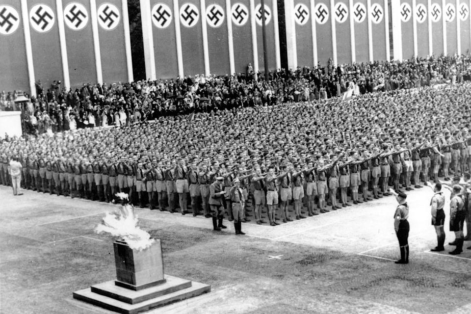 German Nazi soldiers line up at attention during the opening ceremonies of the XI Summer Olympic Games at the Lustgarten in Berlin, Germany on Aug. 1, 1936. The lighted Olympic torch is in the foreground.