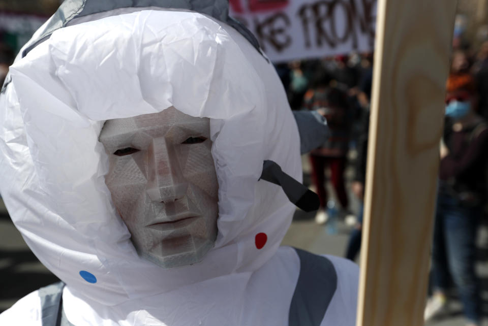 A masked man attends a protest in front of the Serbian Parliament building in Belgrade, Serbia, Saturday, April 10, 2021. Environmental activists are protesting against worsening environmental situation in Serbia. (AP Photo/Darko Vojinovic)