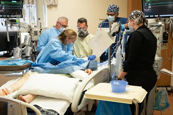 Health care workers in the ICU at Saint Alphonsus Regional Medical Center operate on a patient afflicted with COVID-19. This patient had been intubated with a breathing tube for two weeks, but continued to deteriorate. They have removed the endotracheal tube and are opening the trachea to insert a more permanent tube, a procedure called a tracheostomy.