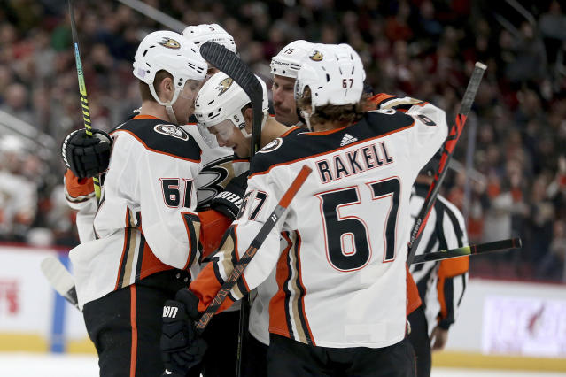Anaheim Ducks Tory Terry (61) and Rickard Rakell (67) and others surround rookie Brendan Guhle (2) after he scored his first NHL goal against the Arizona Coyotes during the first period of an NHL hockey game Wednesday, Nov. 27, 2019, in Glendale, Ariz. (AP Photo/Darryl Webb)