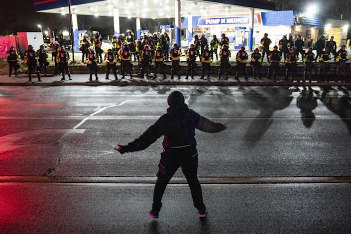 A protester is silhouetted against a line of police in front of a gas station