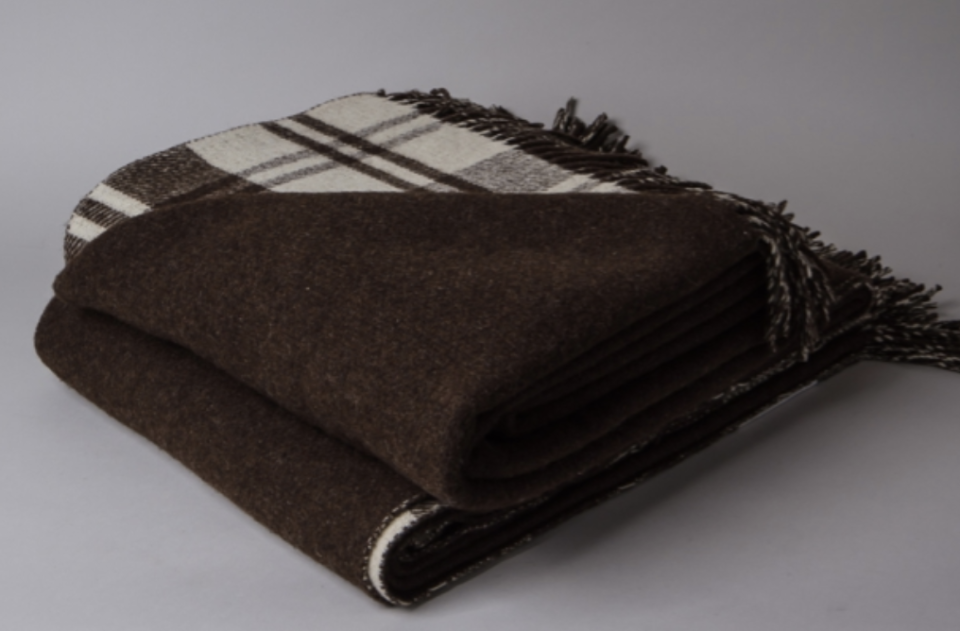 "<p><strong>Saudade</strong></p><p>saudade-shop.com</p><p><strong>£88.00</strong></p><p><a href=""http://saudade-shop.com/product/wool-blanket-double-sided/"" rel=""nofollow noopener"" target=""_blank"" data-ylk=""slk:Shop Now"" class=""link rapid-noclick-resp"">Shop Now</a></p><p>A double sided burel wool blanket made in the Estrela Mountains of Portugal is made of oh so soft merino wool, and gives two options for your decor mood swings: shades of chocolate brown on one side and a plaid on the other.</p>"