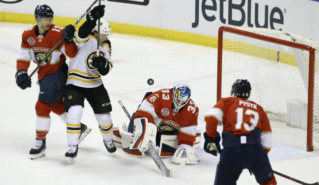 Boston Bruins' Karson Kuhlman, second from left, looks for the puck as Florida Panthers goalkeeper Sam Montembeault (33), Mike Matheson, left, and Mark Pysyk (13) defend during the first period of an NHL hockey game, Saturday, March 23, 2019, in Sunrise, Fla. The Bruins won 7-3. (AP Photo/Luis M. Alvarez)