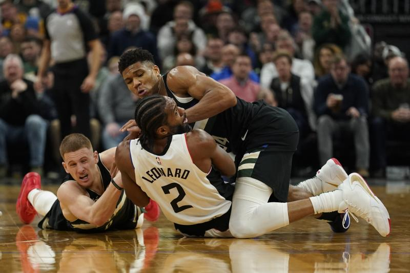 Milwaukee Bucks' Giannis Antetokounmpo and Donte DiVincenzo battle for a loose ball with Los Angeles Clippers' Kawhi Leonard (2) during the second half of an NBA basketball game Friday, Dec. 6, 2019, in Milwaukee. (AP Photo/Morry Gash)