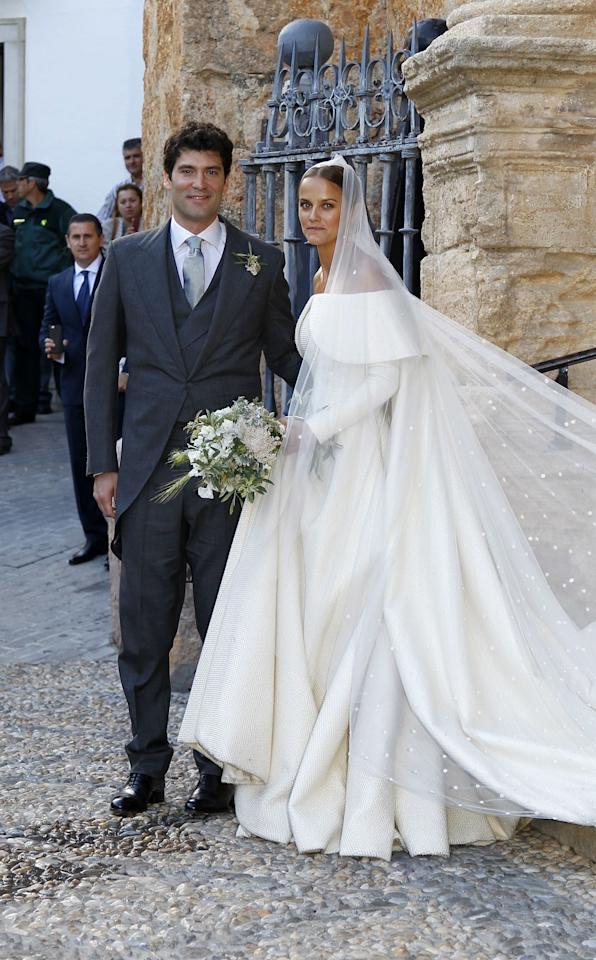 """To wed billionaire financier Alejandro Santo Domingo, Britain's Lady Charlotte Wellesley picked a custom Emilia Wickstead <a rel=""""nofollow"""" href=""""https://www.glamour.com/about/wedding-dresses?mbid=synd_yahoo_rss"""">wedding dress</a> with long sleeves and a draped off-the-shoulder-neckline. The daughter of Princess Antonia, Duchess of Wellington, paired her custom <a rel=""""nofollow"""" href=""""https://www.glamour.com/about/wedding-gowns?mbid=synd_yahoo_rss"""">gown</a> with long veil decorated with pearls."""