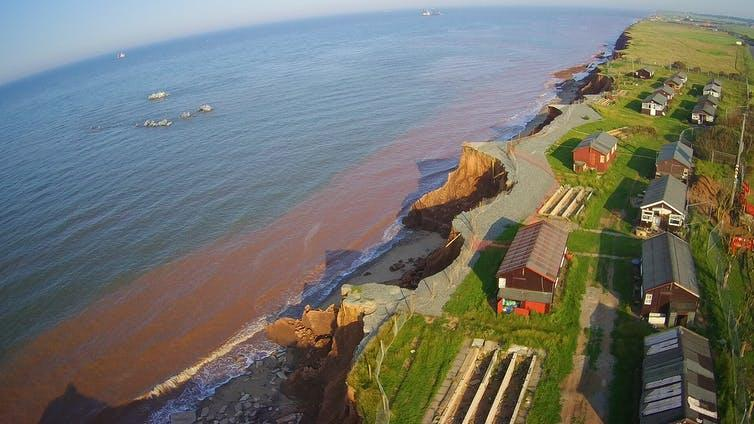 A coastline, edged by houses, showing signs of erosion