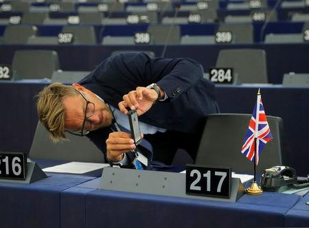 A man takes a picture of a Union Jack flag placed on the desk of a Member of the European Parliament ahead of a debate on BREXIT after the vote on british Prime Minister Theresa May's Brexit deal, at the European Parliament in Strasbourg, France, January 16, 2019. REUTERS/Vincent Kessler