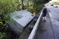 Adam Wirdzek stops to look at a utility building that was carried down a flooded creek Sunday, March 28, 2021, in Nashville, Tenn. Heavy rain across Tennessee flooded homes and roads as a line of severe storms crossed the state. (AP Photo/Mark Humphrey)