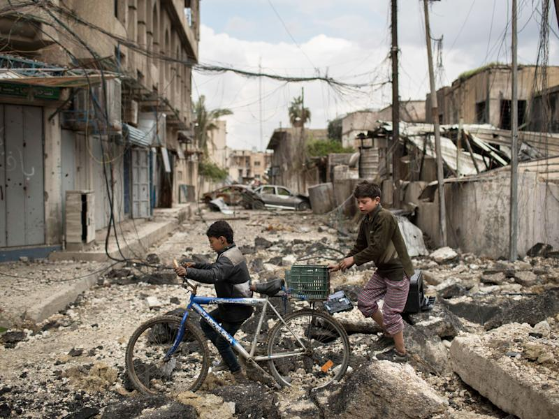 Iraqi boys walk on a destroyed street in a neighborhood recently retaken by Iraqi security forces during fighting against Islamic State militants on the western side of in Mosul: AP