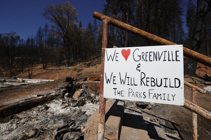 """A sign posted outside a home says, """"We love Greenville and we will rebuild. The Parks family"""""""