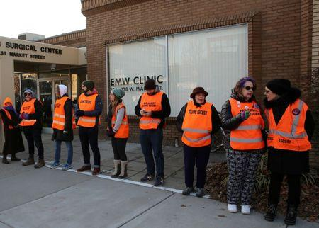 Escorts who ensure women can reach the clinic lineup as they face off protesters outside the EMW Women's Surgical Center in Louisville