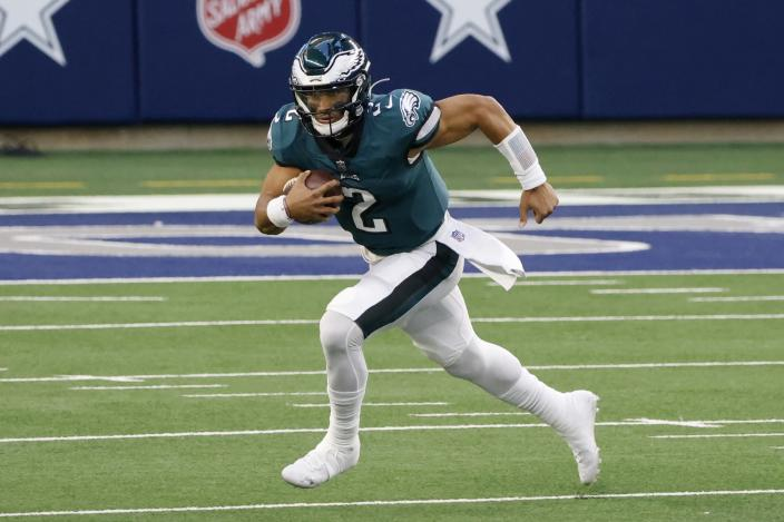 Philadelphia Eagles quarterback Jalen Hurts (2) runs the ball for a first down in the first half of an NFL football game agains the Dallas Cowboys in Arlington, Texas, Sunday, Dec. 27. 2020. (AP Photo/Michael Ainsworth)