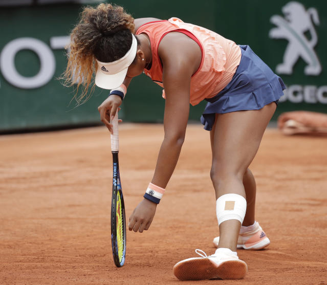 Japan's Naomi Osaka leans on her racket in her third round match against Madison Keys of the U.S. at the French Open tennis tournament at the Roland Garros stadium in Paris, France, Friday, June 1, 2018. (AP Photo/Alessandra Tarantino)