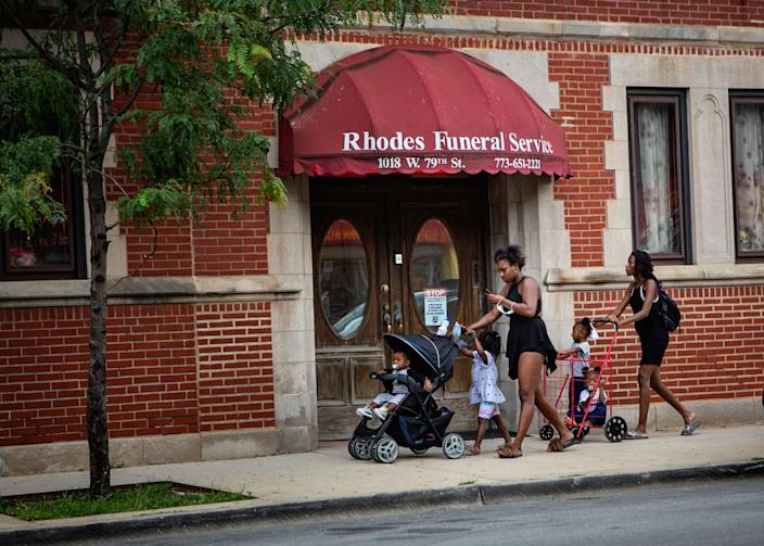 "People walk by Rhodes Funeral Service, where 15 people were shot and injured last week. <span class=""copyright"">(Jason Armond / Los Angeles Times)</span>"