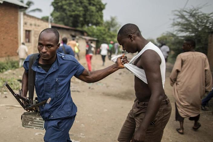 A man is detained by a Burundi policeman during a scuffle with residents angered by a search operation in the of the Cibitoke neighbourhood of Bujumbura on June 27, 2015 (AFP Photo/Marco Longari)