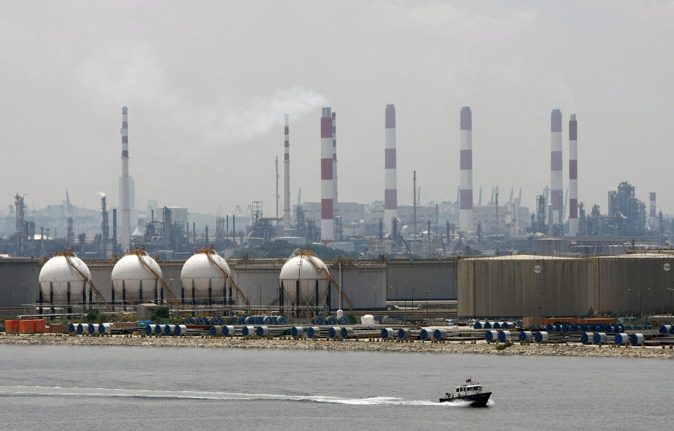A boat passes in front of an oil refinery located on Singapore's Jurong Island March 28, 2009.  REUTERS/Vivek Prakash  (SINGAPORE ENERGY BUSINESS)