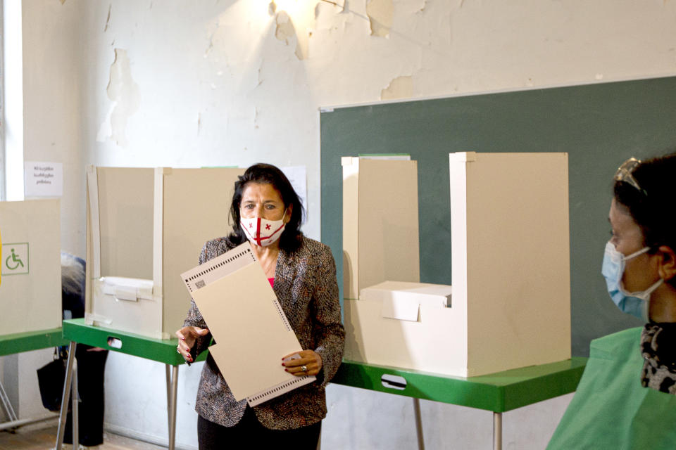 Georgia's President Salome Zurabishvili, wearing a face mask to help curb the spread of the coronavirus, holds her ballot at a polling station during national municipal elections in Tbilisi, Georgia, Saturday, Oct. 2, 2021. Former President Mikheil Saakashvili was arrested after returning to Georgia, the government said Friday, a move that came as the ex-leader sought to mobilize supporters ahead of the national municipal elections seen as critical to the country's political makeup. The elections started Saturday. (AP Photo/Shakh Aivazov)