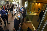 Elizabeth Holmes, bottom center, founder and CEO of Theranos, arrives at the federal courthouse for jury selection in her trial, Tuesday, Aug. 31, 2021, in San Jose, Calif. Holmes faces 12 felony counts alleging she engineered a massive fraud that duped a litany of rich investors with a blood-testing technology that she promised would be able to screen for hundreds of diseases with a finger prick. (AP Photo/Nic Coury)